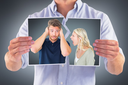 outraged: Man not listening to his shouting girlfriend against grey vignette