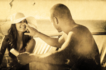 Handsome man applying sun cream on his girlfriends nose against grey background photo