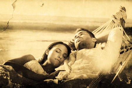 Peaceful couple napping in a hammock against grey background photo