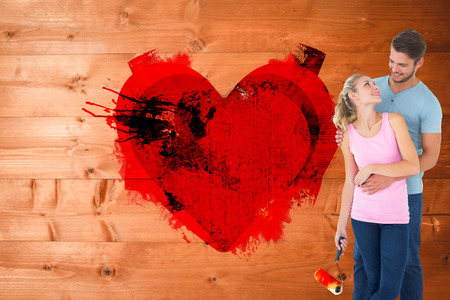 Young couple painting with roller against weathered surface photo