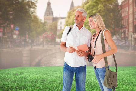 guidebook: Happy tourist couple using the guidebook against sunny day in amsterdam Stock Photo