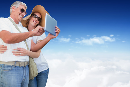 Vacationing couple taking photo against bright blue sky over clouds photo