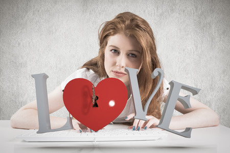 Pretty redhead typing on keyboard  against white and grey background photo