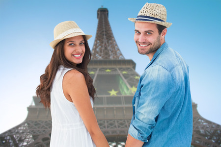 romantic getaway: Happy hipster couple holding hands and smiling at camera against eiffel tower