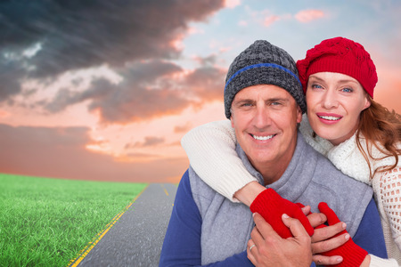warm clothing: Happy couple in warm clothing against road on grass
