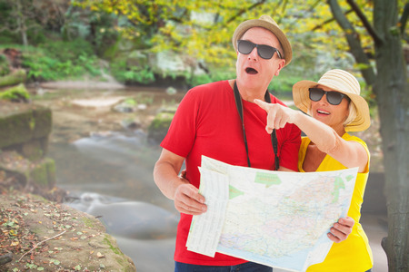 Happy tourist couple using map against rapids flowing along forest photo