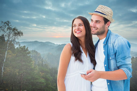 Happy hipster couple smiling together against trees and mountain range against cloudy sky photo