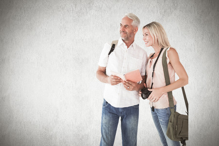guidebook: Happy tourist couple using the guidebook against white background