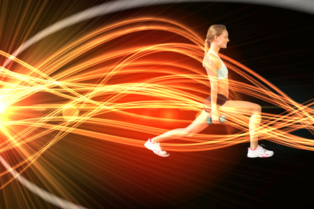lunges: Fit woman doing weighted lunges on the beach against curved laser light design in orange Stock Photo