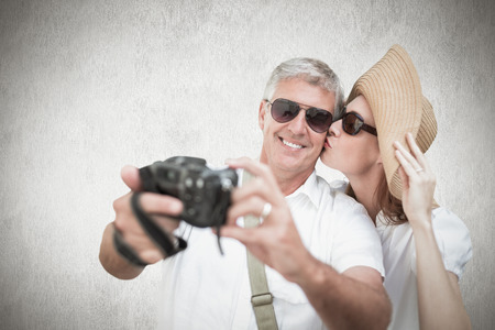 vacationing: Vacationing couple taking photo against white background