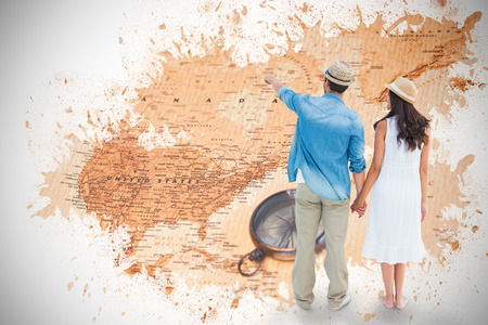 Happy hipster couple holding hands and looking against world map with compass showing north america photo