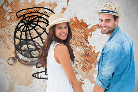 Happy hipster couple holding hands and smiling at camera against world map with compass showing southern asia photo