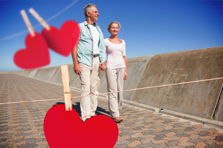 chinos: Happy senior couple walking on the pier against hearts hanging on a line