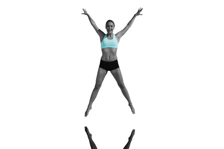 arms out: Fit woman jumping with arms out against mirror