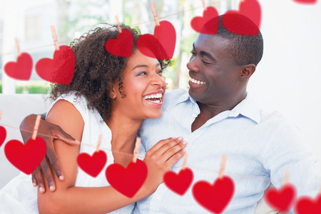 Attractive couple cuddling on the couch against hearts hanging on a line