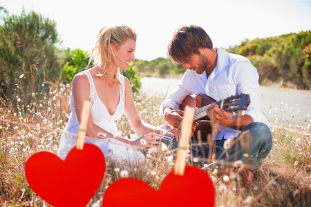 serenading: Handsome man serenading his girlfriend with guitar against hearts hanging on a line
