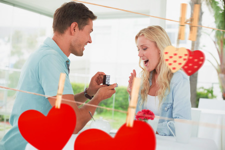 Man proposing marriage to his shocked blonde girlfriend against hearts hanging on the line photo