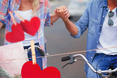 mid adult couple: Hip young couple going for a bike ride against hearts hanging on a line Stock Photo