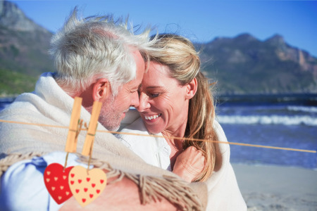 hair wrapped up: Smiling couple sitting on the beach under blanket against hearts hanging on the line