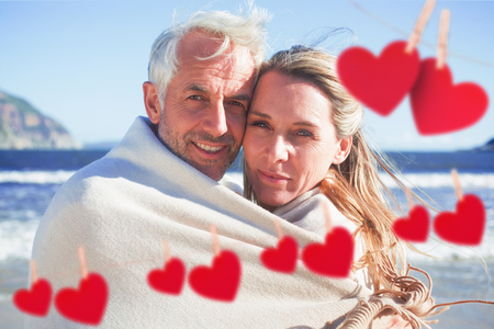 hair wrapped up: Smiling couple wrapped up in blanket on the beach against hearts hanging on a line