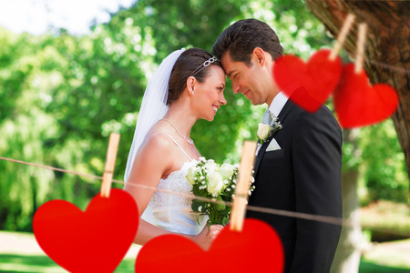 wed: Loving newly wed couple in garden against hearts hanging on a line Stock Photo