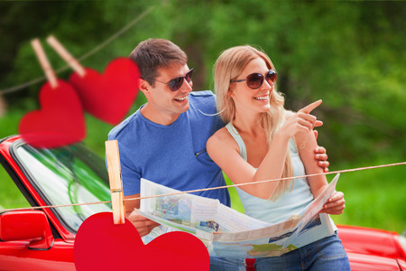 Cheerful young couple reading map against hearts hanging on a line photo