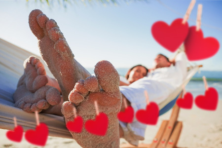 Close up of sandy feet of couple in a hammock against hearts hanging on a line photo