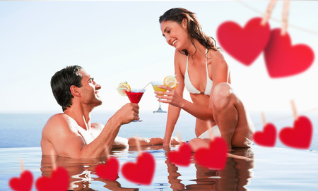 Couple having cocktails in the pool against hearts hanging on a line photo
