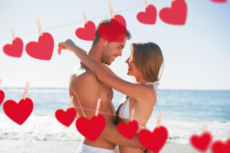Sexy couple embracing against hearts hanging on a line