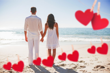 Attractive couple holding hands and watching the waves against hearts hanging on a line photo