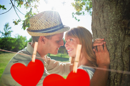 Cute smiling couple leaning against tree in the park against hearts hanging on a line photo