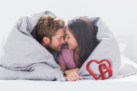 hair wrapped up: Couple wrapped in the duvet against linking hearts