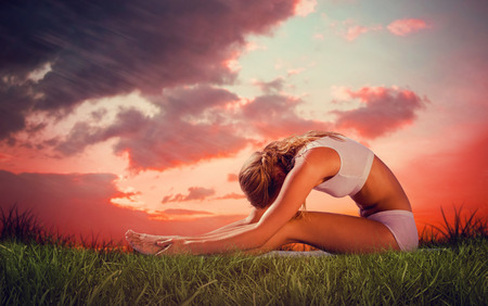 red sky: Gorgeous fit blonde in seated forward bend pose  against red sky over grass