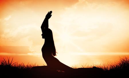 manos unidas: Mujer deportiva con las manos juntas sobre la cabeza en un gimnasio contra amanecer naranja
