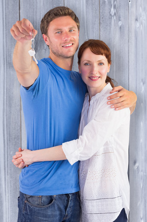 homeowners: Couple holding keys to home against bleached wooden planks background Stock Photo