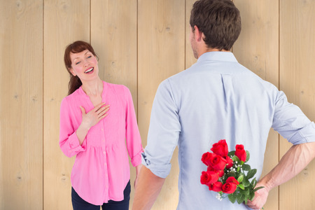 Man holding roses behind him against wooden planks photo