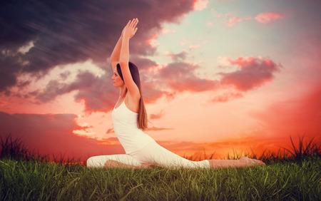 manos unidas: Mujer deportiva con las manos juntas sobre la cabeza en un estudio de la aptitud contra el cielo rojo sobre la hierba Foto de archivo