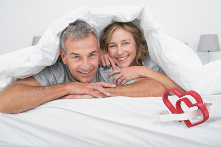 duvet: Cheerful couple under the duvet against linking hearts Stock Photo