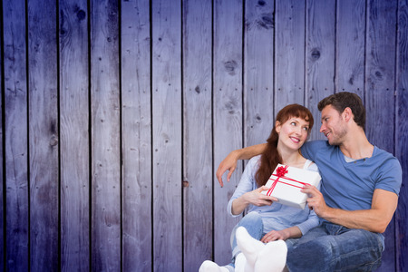 Couple sitting on floor together against wooden planks background Stock Photo