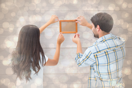 putting up: Happy young couple putting up picture frame against light glowing dots design pattern Stock Photo