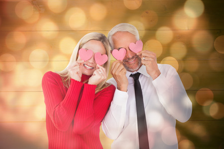 ttractive: Silly couple holding hearts over their eyes against light circles on black background Stock Photo