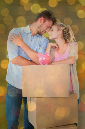 Attractive young couple leaning on boxes with piggy bank against close up of christmas lights photo