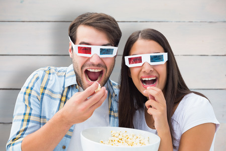 Attractive young couple watching a 3d movie against painted blue wooden planks photo