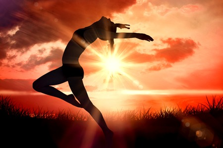 body toning: Side view of a sporty young woman stretching against sunrise over grass Stock Photo