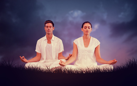 Attractive couple in white meditating in lotus pose against blue sky over grass photo
