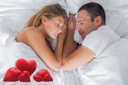 Cute couple lying asleep in bed against love hearts photo