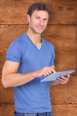 scrolling: Man scrolling through tablet pc against wooden planks