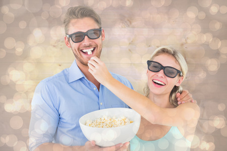 Happy young couple wearing 3d glasses eating popcorn against light glowing dots design pattern photo