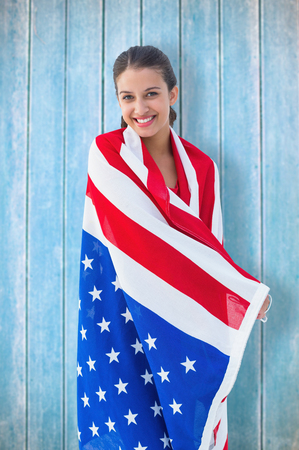 tied hair: Pretty brunette wearing the american flag against wooden planks Stock Photo
