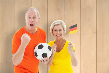 Happy german couple cheering at camera holding ball against wooden planks photo